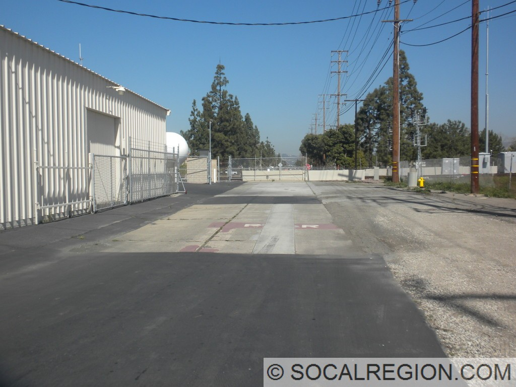 Old alignment of Newport Ave at the Santa Fe Surf Line crossing. Note the R R crossing in red-dyed concrete.