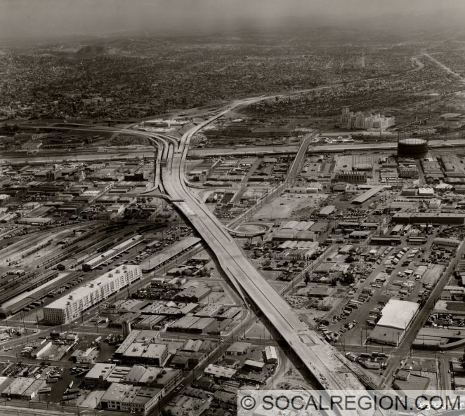 Oblique aerial view easterly along the mostly-completed I-10 Santa Monica Viaduct. Photo was taken by the Division of Highways on September 16, 1961. Viaduct is still under construction west of Alameda Avenue. Loop ramp visible at center connects eastbound Olympic Blvd to eastbound traffic heading to the East Los Angeles Interchange.