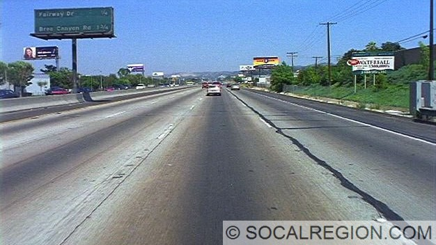 View eastbound along the Pomona Freeway near Puente. The sign to the left marks an interchange that is was never built, Lemon Ave. Photo Courtesy - Caltrans