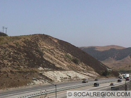 Large zone of fault gouge in road cut at the summit of Tejon Pass on Interstate 5. The gouge is visible as a light colored band within the cut.