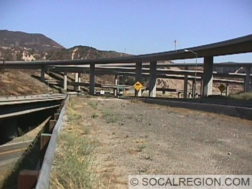 View of the 5/14 interchange from the Weldon Canyon OC. This half of the bridge has been unused since around 1972. View is looking southward. Closest flyover ramp connects SB I-5 to NB SR-14. A span of the old (1975) 5s-14n connector did collapse in the 1994 Reseda/Northridge earthquake.