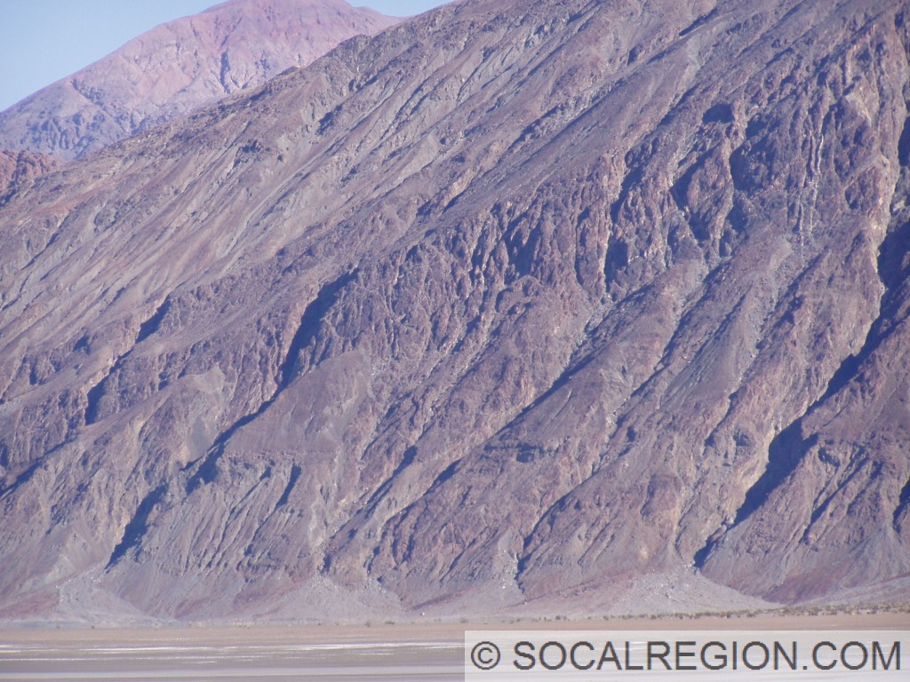 Shorelines visible as horizontal lines on the face of the steep mountain face.